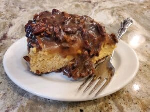 Slice of pumpkin cheesecake with bourbon sauce over top