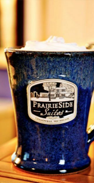 A custom blue mug reads prairieside suites in Grandville, MI
