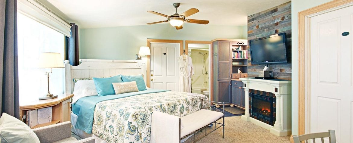 a suite showcases a fireplace next to a kitchenette, a large plush bed, bathrobes, ample seating, and a flat screen tv