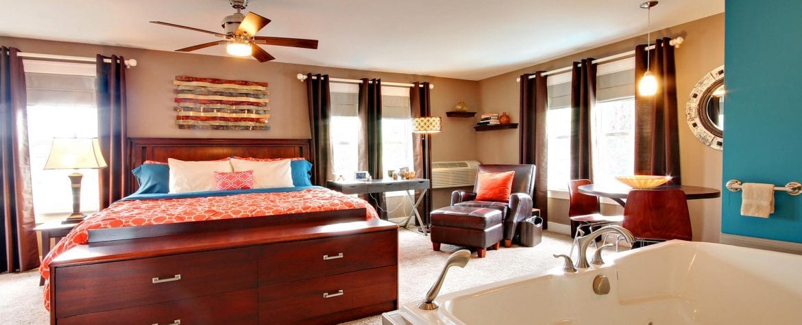 a suite showcases a fireplace next to a kitchenette, a large plush bed, a desk/work area, ample seating, and a luxurious tub.