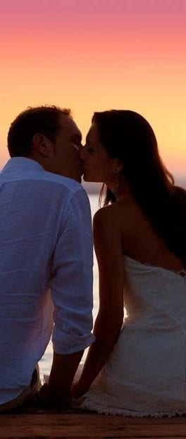 a couple of newlyweds kiss in front of a sunset