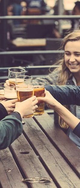 a group of friends hold up beers together